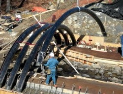 Bridge in a backback technology, workers inflate carbonfiber tubes and fill them with concrete