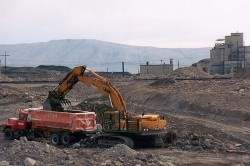 Loading contaminated soil into a truck near the Hanford Nuclear site. A former plutonium production reactor is in the background.