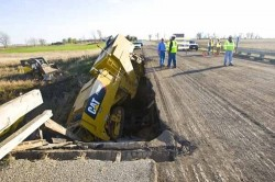 Bridge failure in Minnesota, a 40-ton asphalt milling machine lies in a creek.