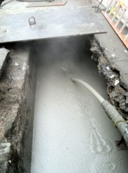 Cellular concrete being flowed into pipeline trench