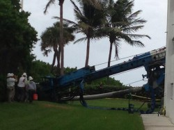 Foundation drill rig laying on its side after toppling and striking adjacent building