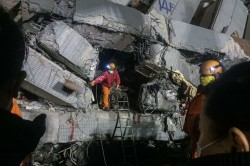 Rescue workers searching through the collapsed building in Taiwan