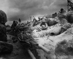 Marines take cover behind a sea wall on Red Beach #3, Tarawa. November 1943.