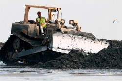 A bulldozer creates a sand berm to attempt to stop oil from reaching the shore  East Grand Terre Island, La.