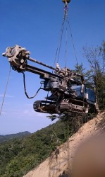 Rock anchor drill rig being flown to the site.