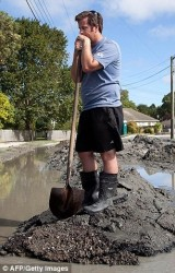 Christchurch New Zealand resident shoveling sand from sand boils that occurred during the earthquake