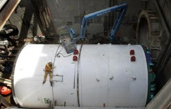 A welder attaches protective shields to one of the two 21-foot-diameter tunnel-boring machines at the north end of the project near Husky Stadium. The entrance to the northbound tunnel is at upper right.