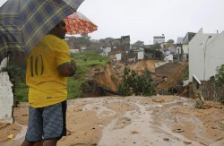Brazil soccer/football fan surveys the landslide damage in Natal