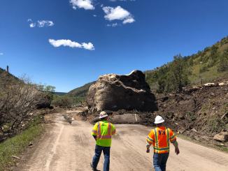 Team members from GSI evaluate one of the massive boulders that fell on Highway 145